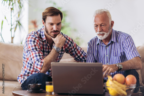 Photo Adult Son Helping Senior Father With Computer At Home