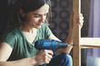 beautiful young woman holding screwdriver and repairing or making wooden shelf