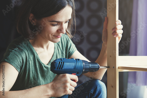Obraz beautiful young woman holding screwdriver and repairing or making wooden shelf - fototapety do salonu