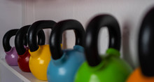 Multi-colored Weights In The Female Fitness Center. Kettlebells Are On The Shelves In The Gym
