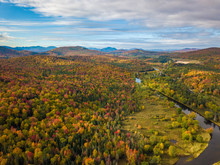 Low Level Aerial Photograph Featuring Fall Foliage In The Adirondack Park Of New York State Featuring Peak Fall Foliage Colors Near Saranac Lake, NY And The Saranac River.