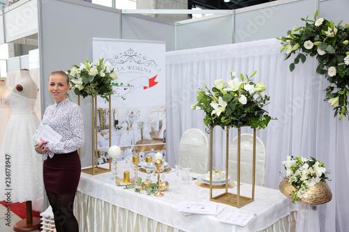 Fototapeta Piękna hostessa prezentuje restaurację na targach ślubnych. obraz