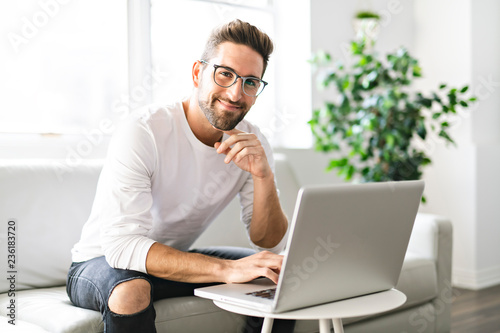 Fototapeta A Young attractive guy is browsing at his laptop, sitting at home on the cozy beige sofa at home, wearing casual outfit obraz