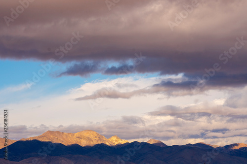 Aluminium Prints Light pink storm clouds over desert mountains