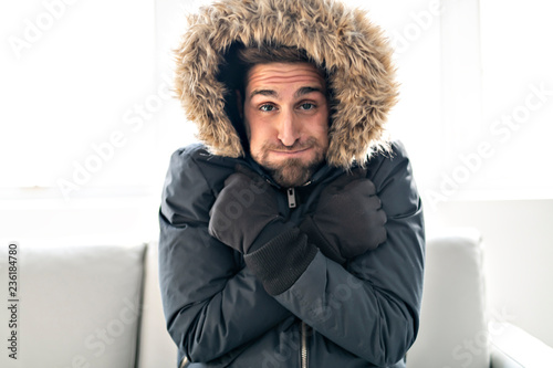 Obraz A Man have cold on the sofa at home with winter coat - fototapety do salonu