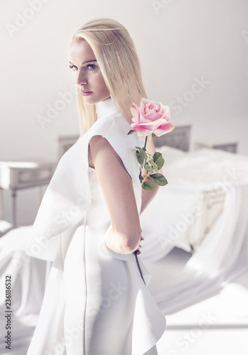 Foto op Canvas Artist KB Elegant, young blonde holding a beautiful pink rose