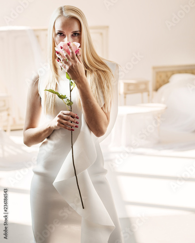 Foto op Aluminium Artist KB Smart blond lady smelling a rose