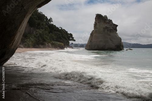 Foto op Canvas Cathedral Cove Wilde Kuste mit Fels im Wasser
