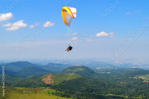 Paragliding in the middle of Auvergne volcanoes mountains