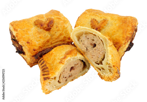 Turkey and cranberry sausage rolls with Christmas holly leaf decoration isolated on a white background