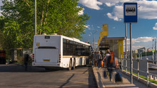 Passengers Waiting And Boarding Buses At The Bus Terminal