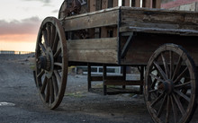 Wooden Coach With Sunset Sky On Background. Rusty Old Western Carriage, Vintage Transportation Concept