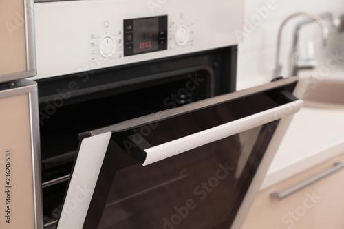 Modern electric oven with open door in kitchen