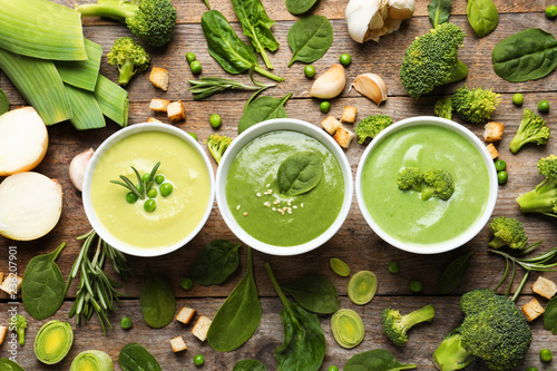 Flat lay composition with different fresh vegetable detox soups made of green peas, broccoli and spinach in dishes on wooden background