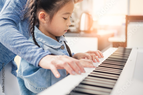 Photo  Asian young pianist teacher teaching girl kid student to play piano, music educa