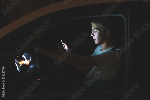 Vászonkép  Distracted teenager driving a car with his cell phone in his hand