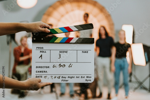Stampa su Tela Woman holding a movie production clapperboard