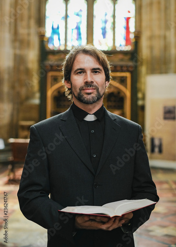 Christian priest standing by the altar Wallpaper Mural
