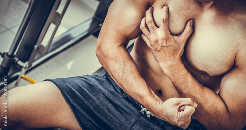 Fotografie, Obraz  Muscular man touching his chest in fitness center