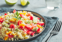 Couscous Salad With Fresh Red And Yellow Bell Peppers, Avocado, Tomatoes And Lime. The Concept Of Vegetarian And Healthy Food.