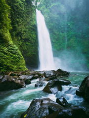Powerful waterfall with river in Bali. Tropical forest and waterfall