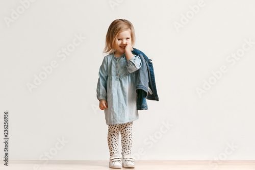 Fototapeta Full length portrait of cute little kid girl in stylish jeans clothes looking at camera and smiling, standing against white studio wall