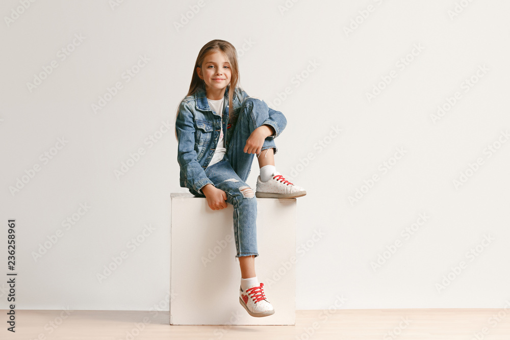 Fototapeta Full length portrait of cute little teen girl in stylish jeans clothes looking at camera and smiling against white studio wall. Kids fashion concept