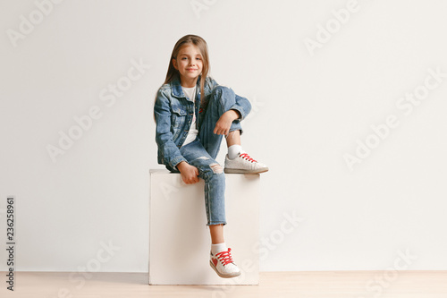 Obraz Full length portrait of cute little teen girl in stylish jeans clothes looking at camera and smiling against white studio wall. Kids fashion concept - fototapety do salonu