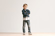 Leinwandbild Motiv The portrait of cute little kid boy in stylish jeans clothes looking at camera against white studio wall. Kids fashion concept