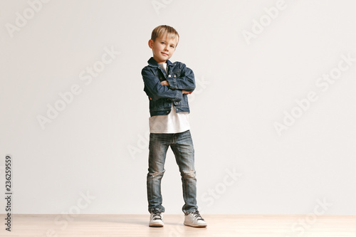 ece25a8a8 The portrait of cute little kid boy in stylish jeans clothes looking at  camera against white studio wall. Kids fashion concept