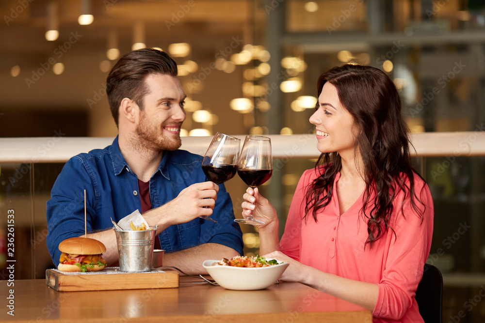 Fototapety, obrazy: celebration, leisure and holidays concept - happy young couple eating and clinking glasses of red wine at restaurant