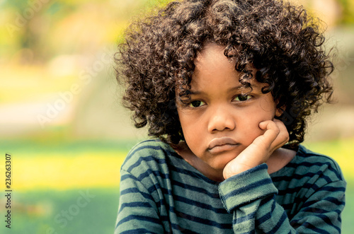 Photo  Unhappy bored little african american kid sitting in the park