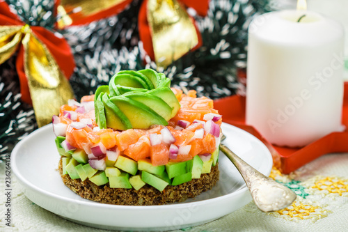 Salmon tartare (trout) with avocado and red onion on rye bread. Appetizer for Christmas and New year. A light snack for gourmets.