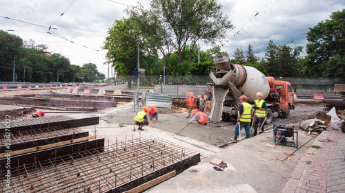 Obraz Concrete works for road maintenance construction with many workers and mixer timelapse - fototapety do salonu