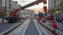 Orange Construction Telescopic Mobile Crane Unloading Tram Rails From Truck Timelapse.