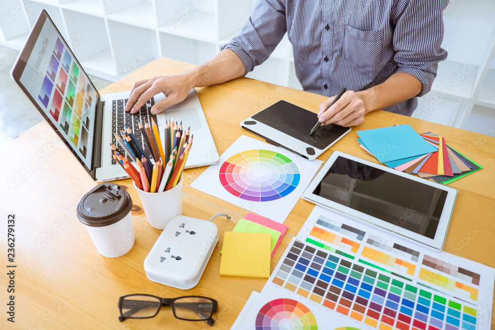 Fototapeta Young creative graphic designer working on project architectural drawing and color swatches, selection coloring on graphic chart with work tools and equipment