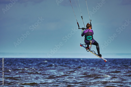 A female kiter jumps over a large lake.