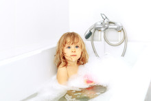 Active Cute Little Blond Toddler Girl Of 2 Years Having Fun With Water By Taking Bath In Bathtub At Home. Funny Kid Splashing And Playing With Toys. Sad Baby In The Shower.