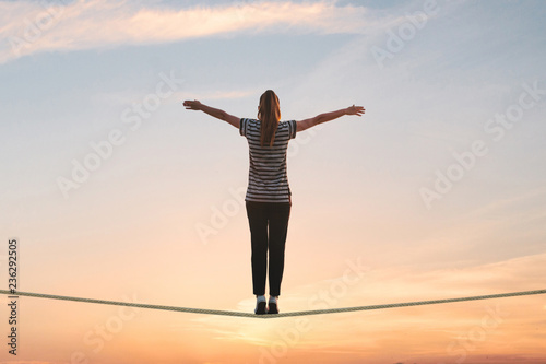 A girl stands on the rope and raises her hands against the sunset Fototapet