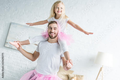 Fototapeta happy father in pink tutu skirt carrying adorable smiling daughter on neck