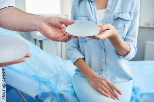 Obraz Close up photo of doctor showing silicone implant for woman during consultation in beauty clinic - fototapety do salonu