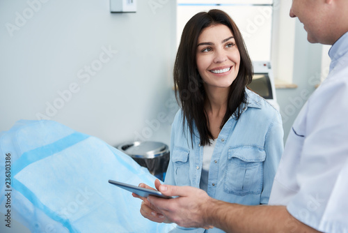 Fotomural  Plastic surgeon giving tablet to female patient to filling out questionnaire in clinic of beauty