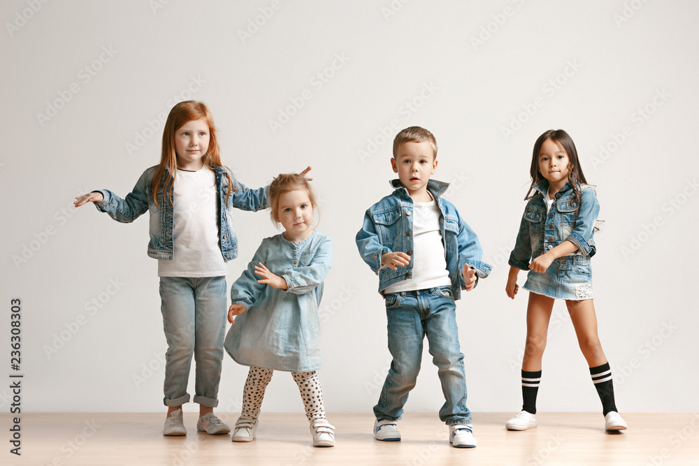 Fototapeta The portrait of cute little kids boy and girls in stylish jeans clothes looking at camera against white studio wall. Kids fashion and happy emotions concept