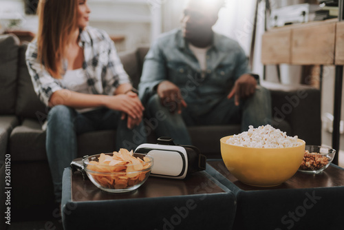 Close up of virtual reality glasses and bowls with popcorn and chips on table. Beautiful girl and afro american guy sitting on couch on blurred background