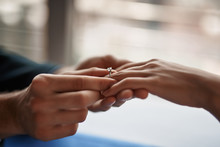 Concept Of Engagement. Close Up Portrait Of Young Gentleman Putting Ring On Finger Of His Beloved Woman