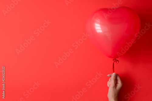 Photo  Hand holding a red heart balloons on red paper background