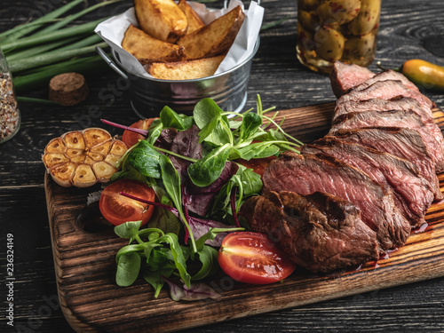 sliced juicy steak medium rare on the board with herbs, fried potatoes, spices on a black surface