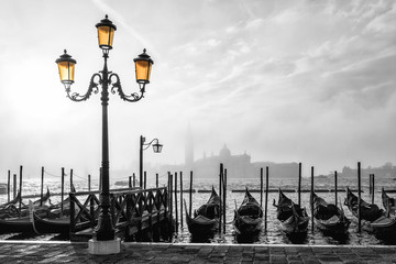 Fototapeta Wenecja Black and white photo of gondolas in Venice at sunrise with Saint Giorgio island in morning fog, as seen from San Marco square