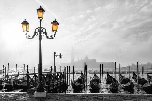 Fototapeta Black and white photo of gondolas in Venice at sunrise with Saint Giorgio island in morning fog, as seen from San Marco square obraz