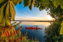 Kayaking On A Blue Lake At Beautiful Sunset